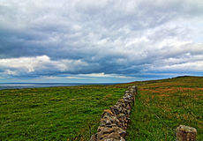 Stone fence in the pasture lands near the  Cliffs of Moher in Country Clare Royalty Free Stock Image