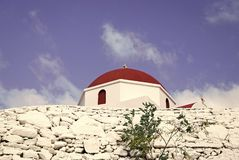 Stone fence and red dome with cross detail in Mykonos, Greece. Church building architecture on sunny outdoor. Chapel on. Blue sky. Religion and cult concept royalty free stock images