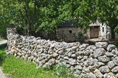 Stone fence and rustic old abandoned house Royalty Free Stock Photo