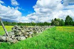 Stone fence separating farm grounds. Traditional stone fence separating farm grounds in Swedish country side. This fence was build probably built some hundreds Royalty Free Stock Images