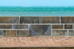 Stone fence wall and pavement next to the sea Royalty Free Stock Photos