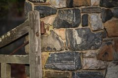 Stone fence with wooden gate. Textures of stone fence and wooden gate. Found in Pennsylvania where stone is used a lot in construction stock photo