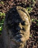 Stone figurine. Face in the garden, stone portrait Stock Photo