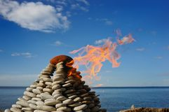 Stone fire. Burn stone pyramid on the bank of northern sea Stock Photos