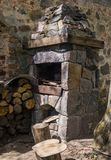 Stone fireplace for frying meat, laid out on the street against the wall, along with firewood royalty free stock images