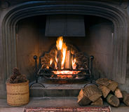 Stone fireplace with a lit roaring fire Royalty Free Stock Images