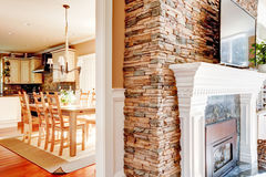 Stone fireplace with tv and dining room and kitchen. Royalty Free Stock Images