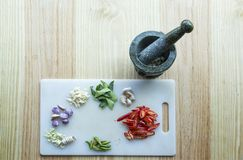Stone flait and mortar hit thai herb ingredient on wood table in Royalty Free Stock Photos