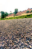 Stone floor outside with round gravels near a road Royalty Free Stock Photo