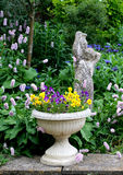 Stone Flower container with pansies and a stone st Royalty Free Stock Image