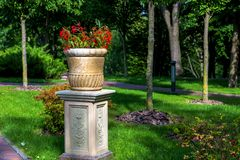 Stone flower pot on a stone pedestal with flowers. stock photography