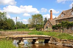 Stone footbridge over river, Lower Slaughter. Royalty Free Stock Photography