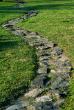 Stone footpath in the garden. Stone footpath on the grass in the garden Royalty Free Stock Image