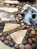 Stone footpath through pebble gravel in rock garden Royalty Free Stock Photos