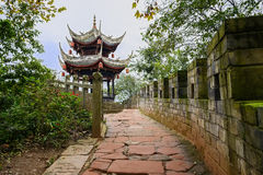 Stone footway and brick parapet before ancient Chinese gazebo in Royalty Free Stock Image