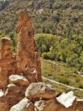 Stone Formation above Ruins in Frijoles Canyon. A large stone spire rises high above the ancient ruins located in Frijoles Canyon.  Bandelier National Monument Royalty Free Stock Images