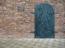 Old iron door with a stone wall royalty free stock image