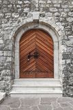 The stone fortress wall of the castle of the medieval castle, an old wooden closed door with a lock. Stock Images