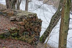 Stone foundation of a ruined old house on the river bank Stock Images
