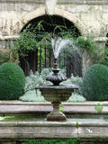 Stone fountain in classical garden. Old stone working fountain in classical renaissance walled courtyard garden with shrubs and stonework royalty free stock images