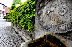 Stone fountain and paved road Stock Photography