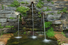 Stone fountain. With three jets of water falling Stock Photo