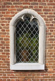 Stone Framed Window. A neo Gothic stone framed window in brick wall of Tongerlo Abbey with leaded glass pane and plant pot on interior window sill stock photo