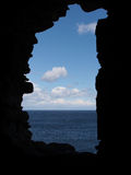 Stone framing. Sea and sky seen through a hole in a stone wall Stock Photo