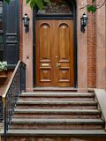 Old urban brownstone type townhouse with polished double wooden door. Stone front step of elegant old urban brownstone type townhouse with polished double wooden stock photos