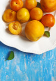 Stone fruits on plate. Yellow plums, apricots and nectarines Stock Image