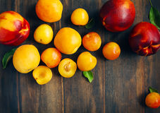 Stone fruits on wooden background. Yellow plums, apricots and nectarines Stock Photo