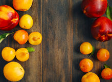 Stone fruits on wooden background. Yellow plums, apricots and nectarines Stock Image