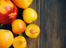 Stone fruits on wooden background. Yellow plums, apricots and nectarines Stock Photography