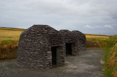 Stone furnaces also known as huts in Ireland. Against a golden crop and cloudy sky Royalty Free Stock Image