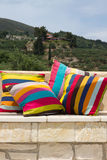Stone garden bench with colorful pillows Stock Images