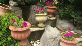 Stone garden vase. Violet flowers. Water flow Royalty Free Stock Image