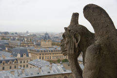 Stone gargoyle overlooking Paris from the Notre Dame Stock Images