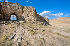 Stone Gate of the fortress with crumbling walls and huge bricks of the old grungy town in the desert valley Royalty Free Stock Images
