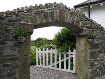 A stone gate with a white wooden door. Leads to a flower garden Stock Photography