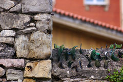 Stone and glass. A stone wall with green glasses, selective focus and sunlight Stock Photos