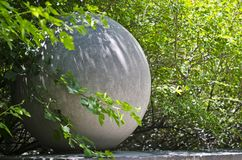 A stone globe in the park trees stock image