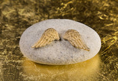 Stone with golden angel wings: greeting card for die, death, com. Munion or baptism Stock Image