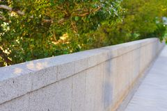 Stone gray fence in the park royalty free stock photo