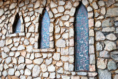 Stone gray wall with three narrow windows in the shade of trees Royalty Free Stock Photography