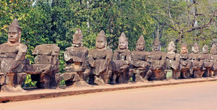 Stone Guard Statues. Row of Stone Guard Statues at the entrance of Angkor Thom Temple Royalty Free Stock Photos