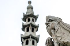 Stone guardian and blured stone pagoda Royalty Free Stock Images