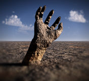Stone Hand. A conceptual image of a stone hand reaching out of the ground in a barren unfertile landscape Stock Image