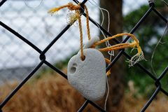 A stone that has been worn by the tide is tied to a fence through a natural hole. stock photos
