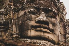 Lichen-covered Stone Head Statue in Angkor Wat, Siem Reap, Cambodia, Indochina, Asia - face on in colour stock photo