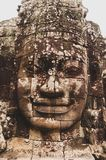 Lichen-covered Stone Head Statue Face-On in Angkor Wat, Siem Reap, Cambodia, Indochina, Asia - face on in colour. Stone head in Angkor Wat, Cambodia, Indochina royalty free stock photography